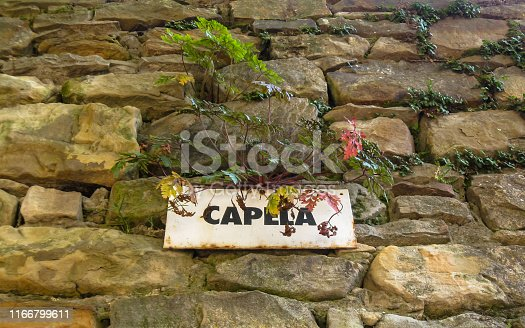 Engraved metal plate - Chapel on a stone wall. Above the plate the vegetation managed to make its presence.