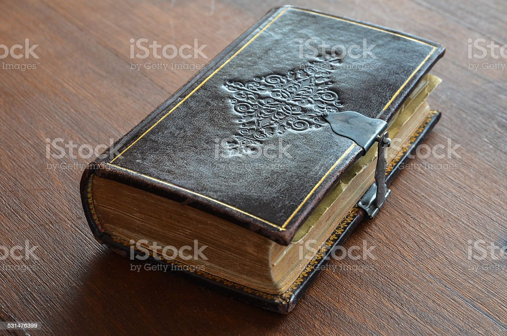 engraved old book with lock on wood table stock photo