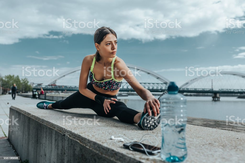 Beautiful young sportswoman doing a split outdoors
