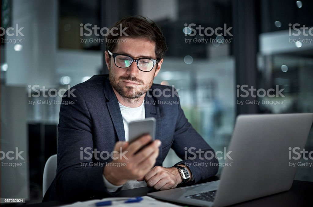 Enhancing his entrepreneurial ambition with the right tools Shot of a young businessman using his laptop and phone at work Adult Stock Photo