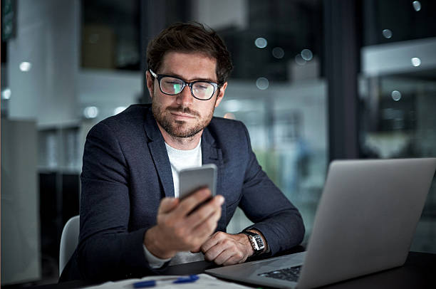 Enhancing his entrepreneurial ambition with the right tools Shot of a young businessman using his laptop and phone at work business laptop stock pictures, royalty-free photos & images