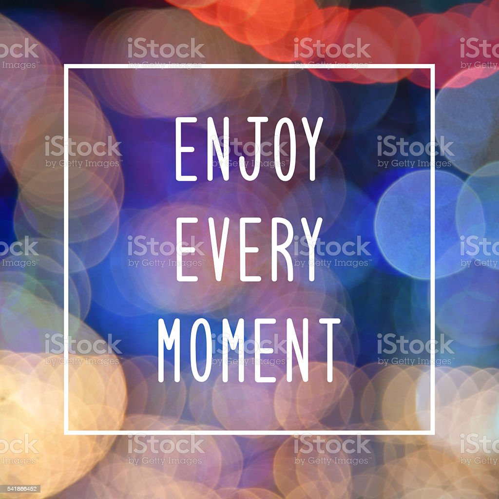 Enjoy every moment text on bokeh lights background stock photo