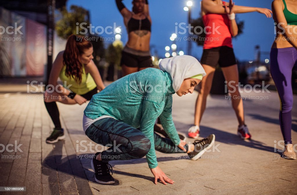 Multi ethnic group of young women exercise outdoor at night. They are...