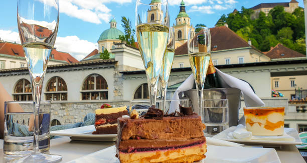 Enjoy Ljubljana's cake and drink Close up of glasses of champagne and cakes at Triple bridge promenade at Ljubljanica river. ljubljanica river stock pictures, royalty-free photos & images