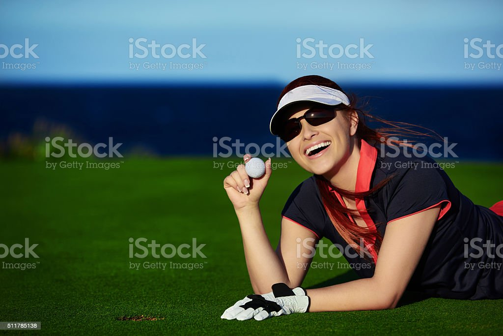 portrait of young woman holding golf ball and smiling, feeling glad...