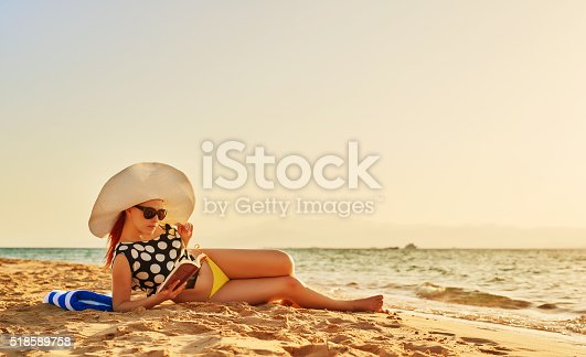 side view of young woman lying in the beach and reading a book, feeling great and relaxing in her summer day.