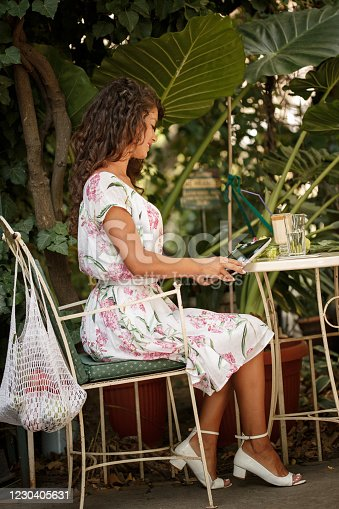 Side view of a young woman in light dress sitting on an outdoors coffee shop  after buying groceries with hre reusable shopping bag. She is holding the menu on her hand while checking it.