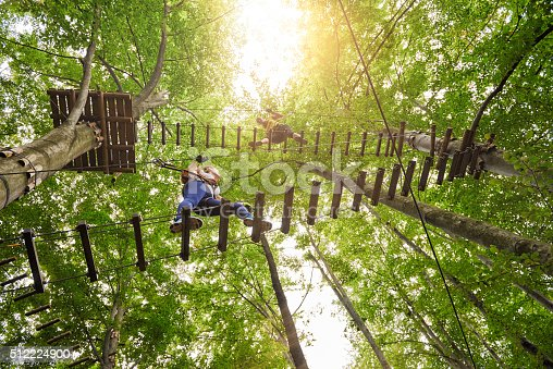 low angle view of three friends in adventure park climbing on suspension bridge.summer day.
