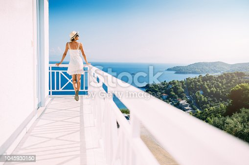 Rear view of travel girl posing on the Mediterranean island house terrace.
