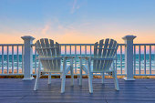 Two empty Adirondack chair on a balcony deck overlooking the beach and the ocean in the Outer Banks of North Carolina