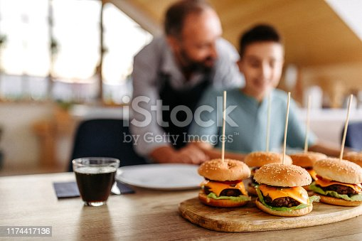Father serving homemade burgers to his son for dinner, in the dining room