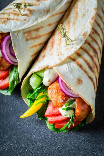 genießen sie ihr gegrilltes tortilla mit frischem gemüse und hühnerfleisch - veggie wraps stock-fotos und bilder