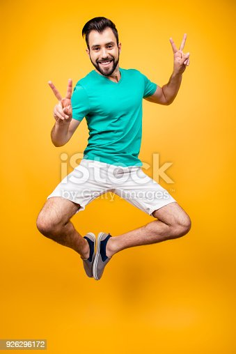 istock Enjoy your life! Vertical front view full size portrait of happy amazed cheerful joyful smiling man in tshirt and shorts, he is jumping up, demonstrating v-signs, isolated on bright yellow background 926296172