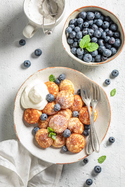 Enjoy your poffertjes with fresh berries and powdered sugar stock photo