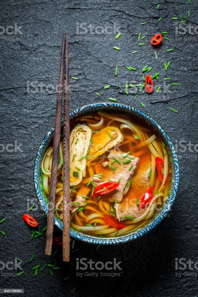 Enjoy your Red Curry soup with chopsticks on black rock stock photo