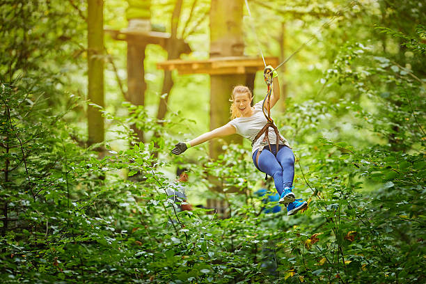 enjoy zipping in forest photo of young woman in adventure park having fun in tyrolean traverse and enjoying her active day.summer season. zip line stock pictures, royalty-free photos & images