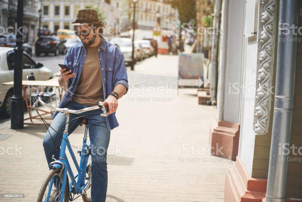Enjoyed guy sitting on bike with device - Royalty-free Adult Stock Photo