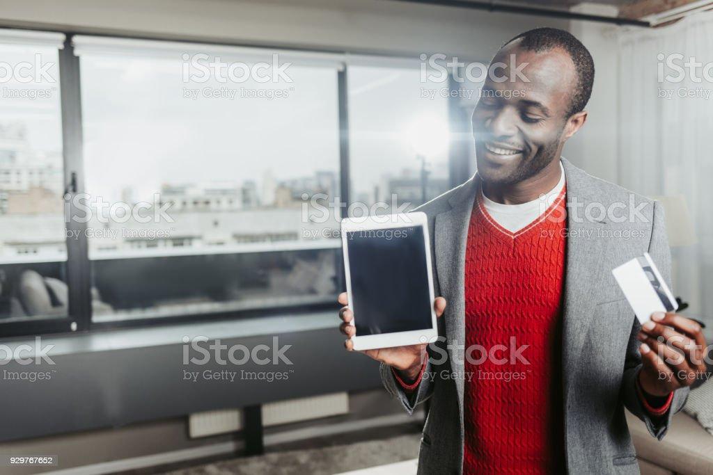 Enjoyed man demonstrating tab and bankcard stock photo