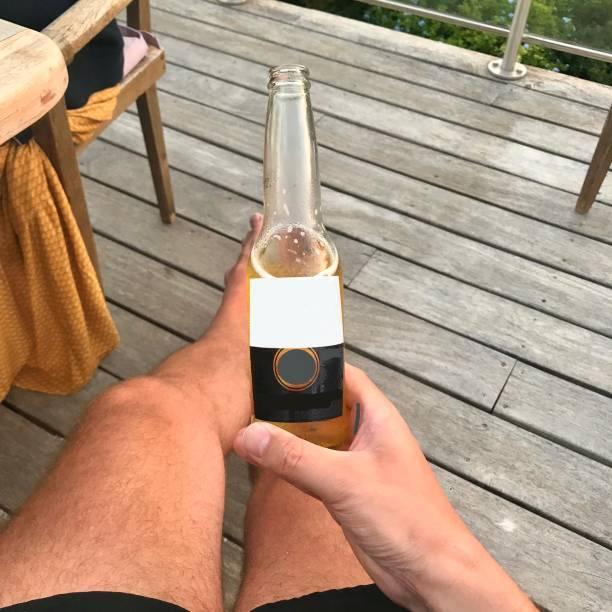 Enjoying a beer on the balcony. stock photo