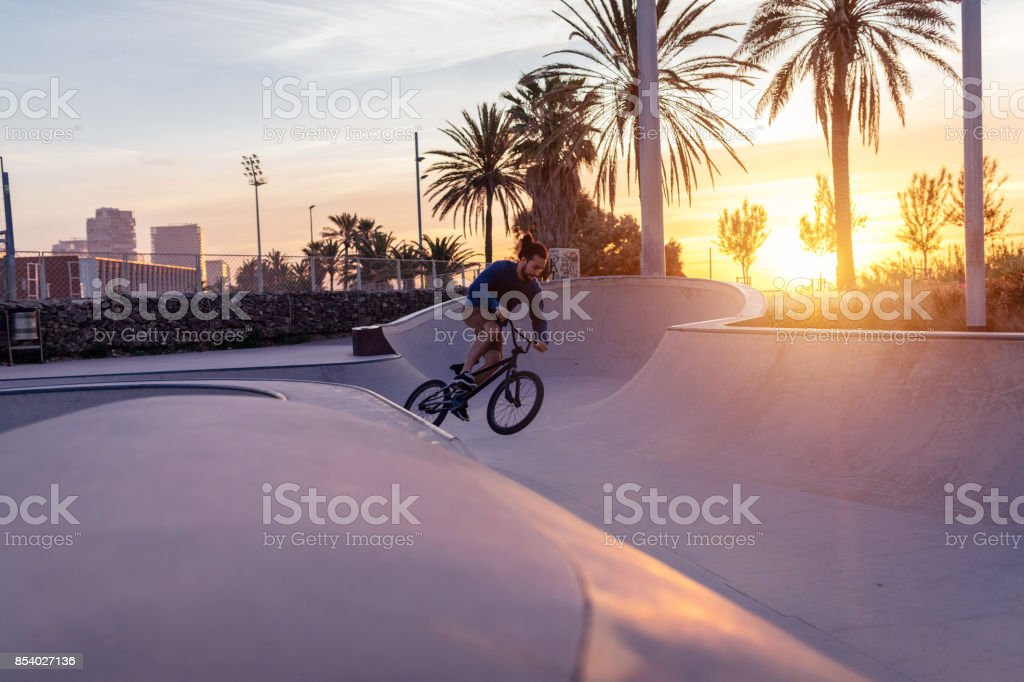 Shot of a man doing tricks on his bike, with sun flare.