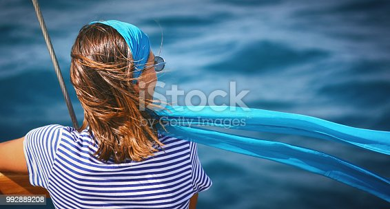 Closeup rear view of a mid 20's woman on a sailboat looking at the distance while her headscarf is flapping in the wind. Copy space on the right.