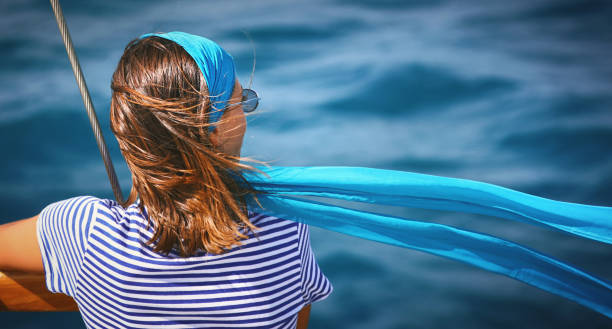 Enjoying a boat cruise. Closeup rear view of a mid 20's woman on a sailboat looking at the distance while her headscarf is flapping in the wind. Copy space on the right. headscarf stock pictures, royalty-free photos & images