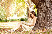 A beautiful woman sitting against a tree and reading a book