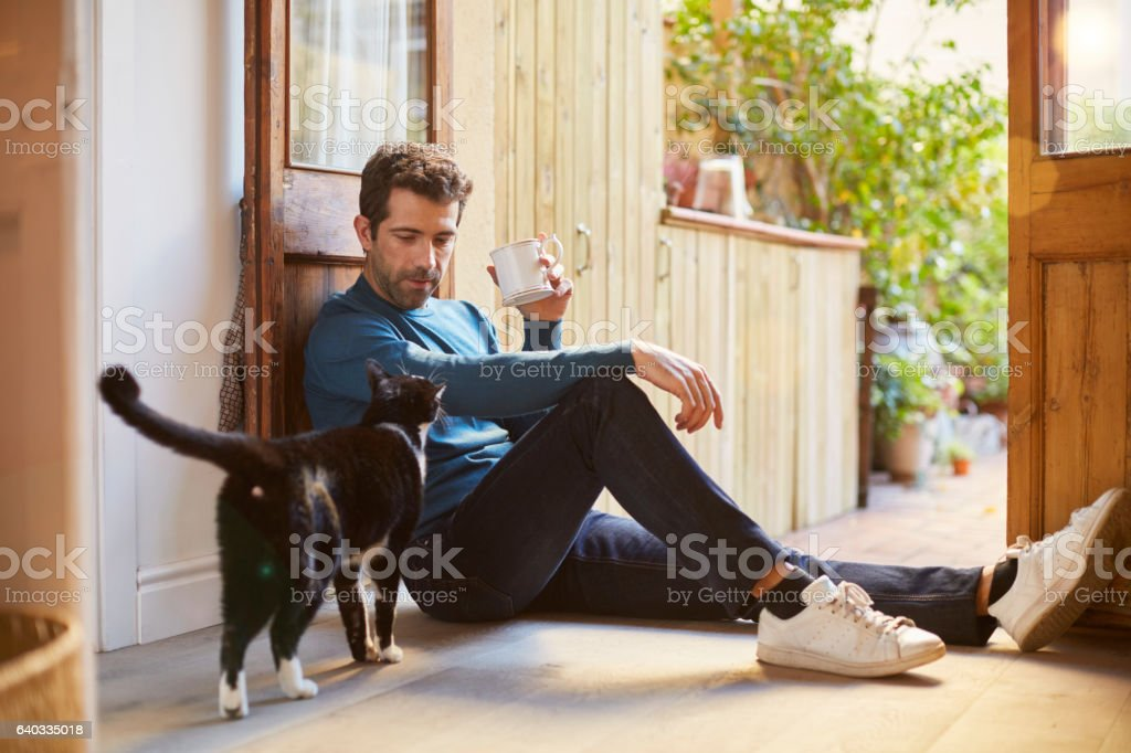 Enjoying a cup of tea sitting on the ground. stock photo