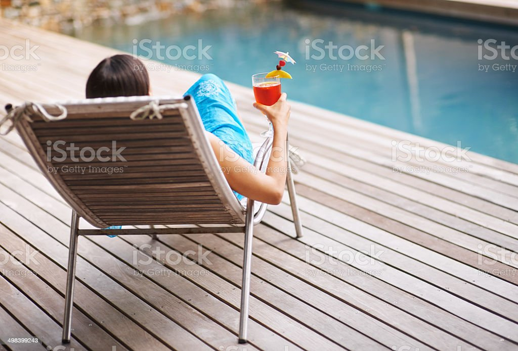 Enjoying a drink on the pool deck stock photo