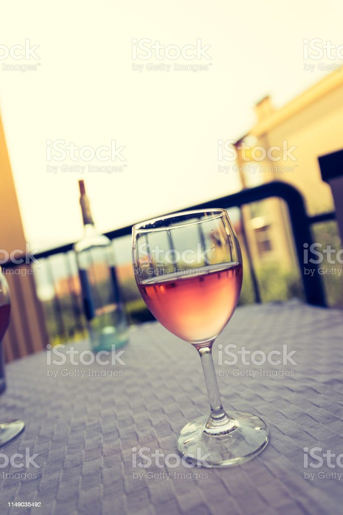 Glass of rose wine outdoors on the balcony. Evening scenery, Italy