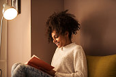 African american girl reading a book at home.
