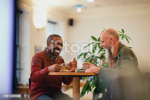 Two senior men are relaxing in a modern cafe, laughing and talking while enjoying green tea.