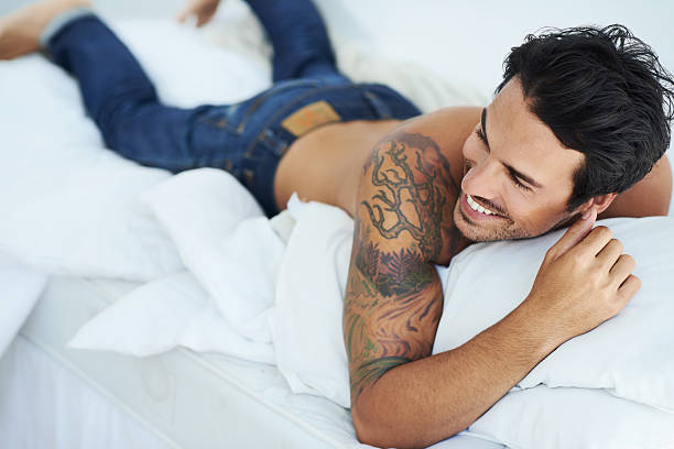Enjoying a laugh in bed Shot of a happy-looking young man lying on his stomach in bed shirtless male models stock pictures, royalty-free photos & images