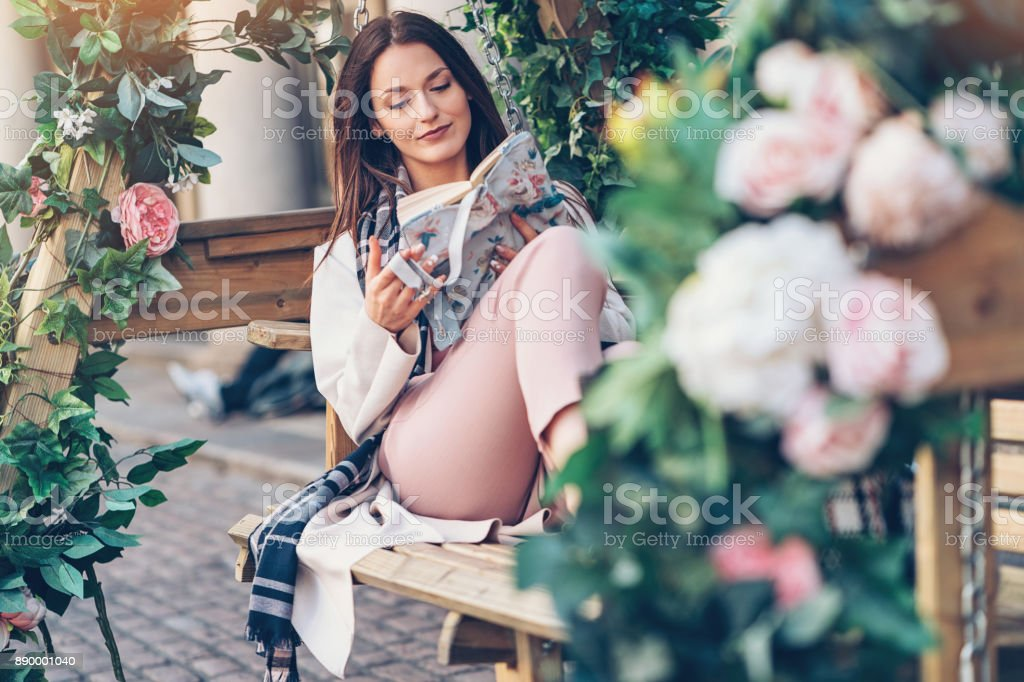 Enjoying a nice book and rose scent stock photo