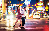 A couple rushing across the street in Las Vegas, Nevada, with bright city lights in the background.