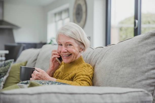 bénéficiant d'un appel téléphonique et une tasse de thé - seulement des femmes seniors photos et images de collection