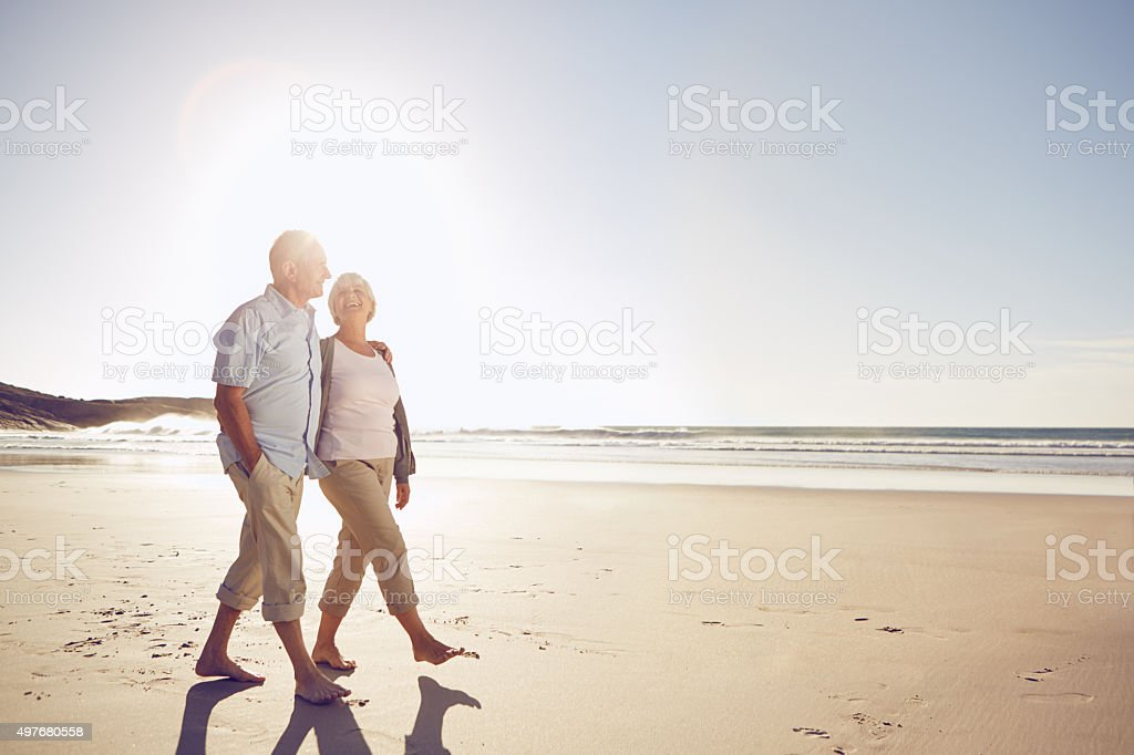 Enjoying a romantic walk on the beach stock photo