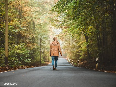 Photo of single man walking or leaving through a forest landscape in a country road during autumn day. Rear view of Man walking through woods with light ahead,  after the rain stopped and the sun now shines through the forest.
