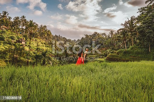 Photo of Young beautiful woman and woman walking and falling in love on the traditional rice terraces in Tegallalang, Ubud, Bali. She is wearing a red dress and holding the hand of her boyfriend.