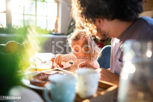 Little girl having breakfast with her dad at home, eating marmalade