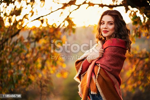 Portrait of a beautiful young caucasian woman enjoying a carefree autumn day in nature.