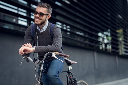 Handsome hipster enjoying city ride by bicycle.