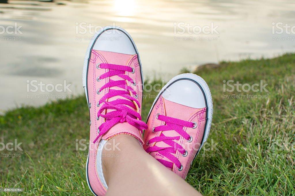 Enjoying by lake. Woman wearing pink sneakers royalty-free stock photo