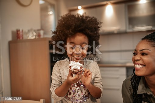 Cute 5 years old girl enjoying in Christmas sweets.