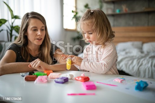 Little girl playing with modeling clay in bedroom with her mom