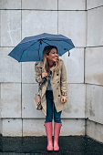 Full length portrait of a woman with an umbrella outdoors in the city.