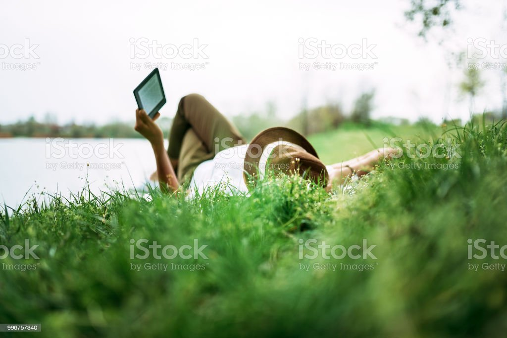 Enjoying e-book near the lake. Girl lying in the grass. foto stock royalty-free
