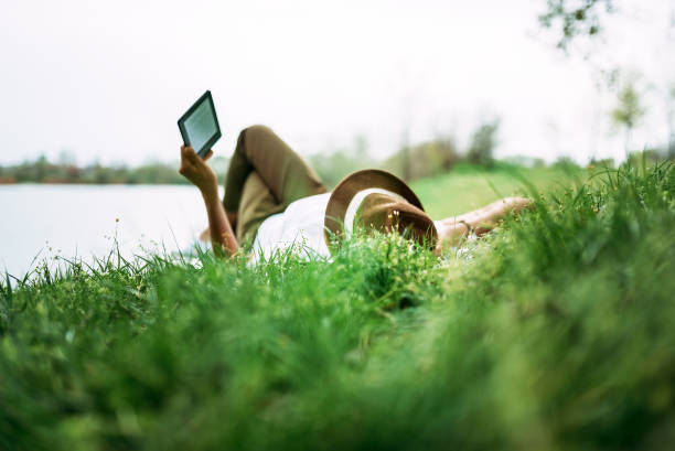 Enjoying e-book near the lake. Girl lying in the grass. stock photo