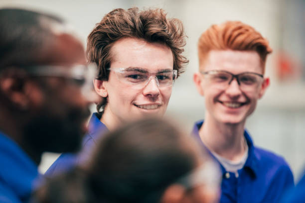 Enjoying Engineering Class A young man, who is wearing protective eyewear, smiles as he enjoys his engineering class with peers - they are all wearing blue coveralls. apprentice stock pictures, royalty-free photos & images