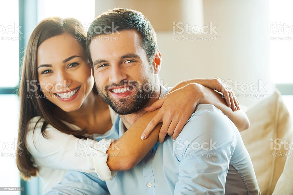 Beautiful young loving couple sitting together on the couch while...